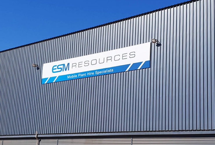 The ESM Resources building roof with the sign attached & blue sky.