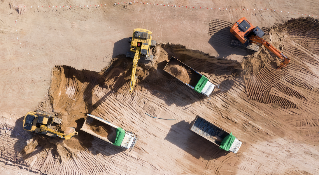 A birds eye view of an open pit mine site with machines.