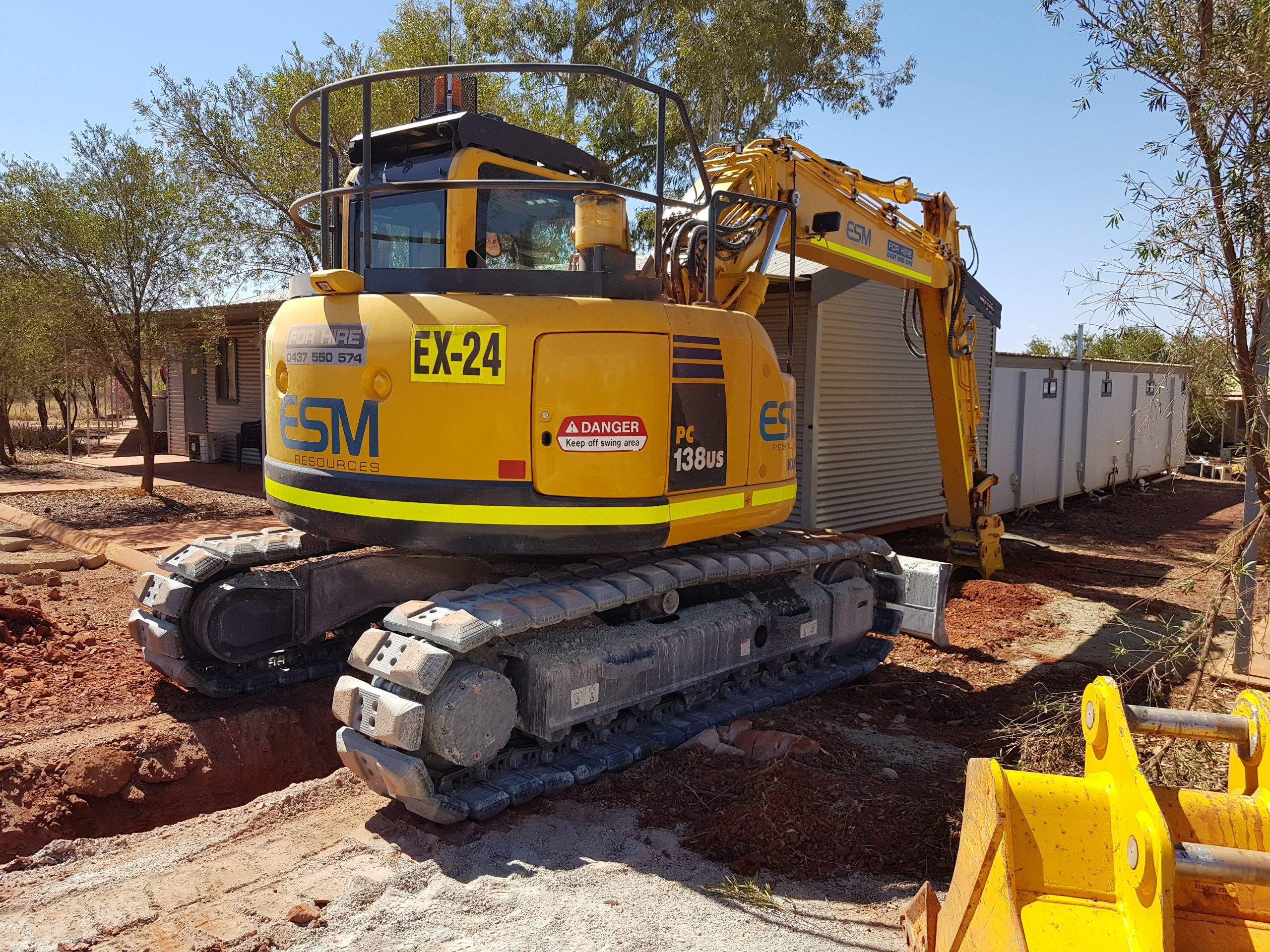 A excavator from ESM Resources working at a mining camp.