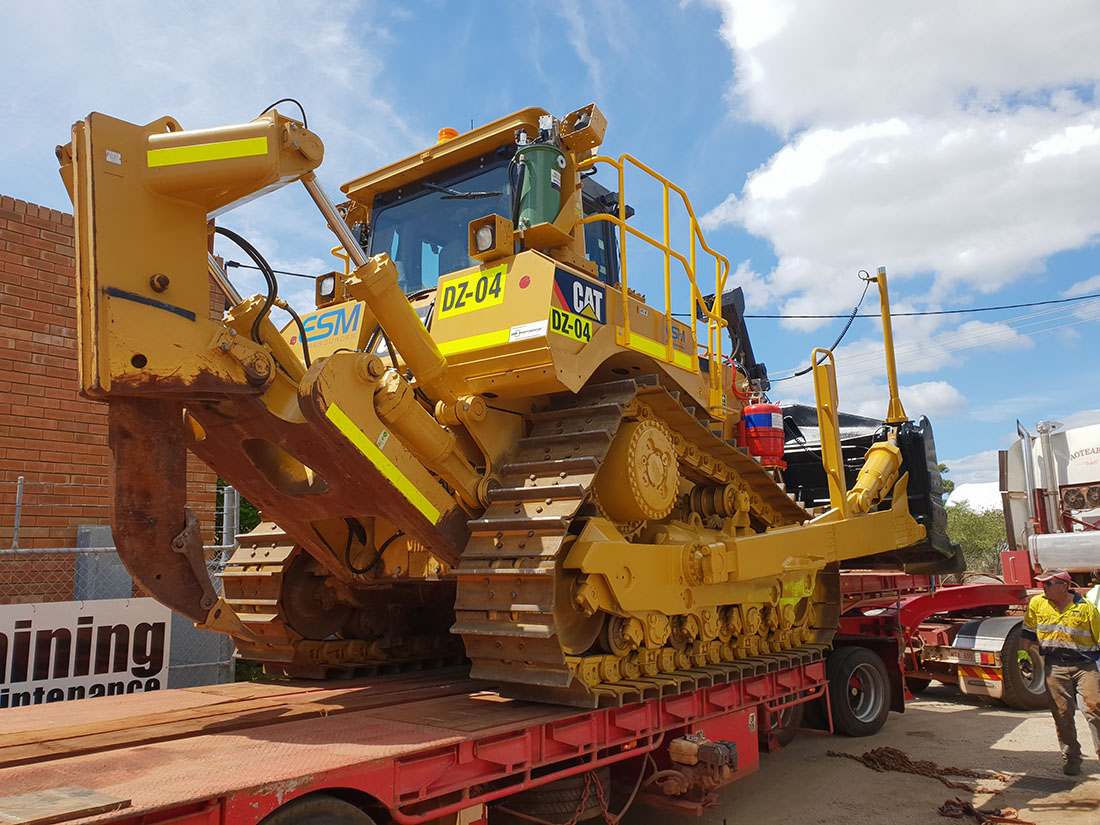 A bulldozer coming back for service on the back of a truck trailer.