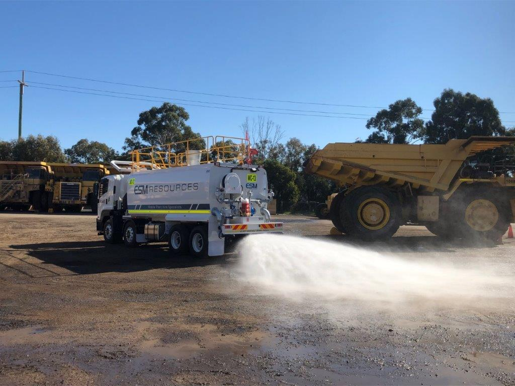 A hired water truck spraying on the dusty ground on a mine site with dump trucks in the background.