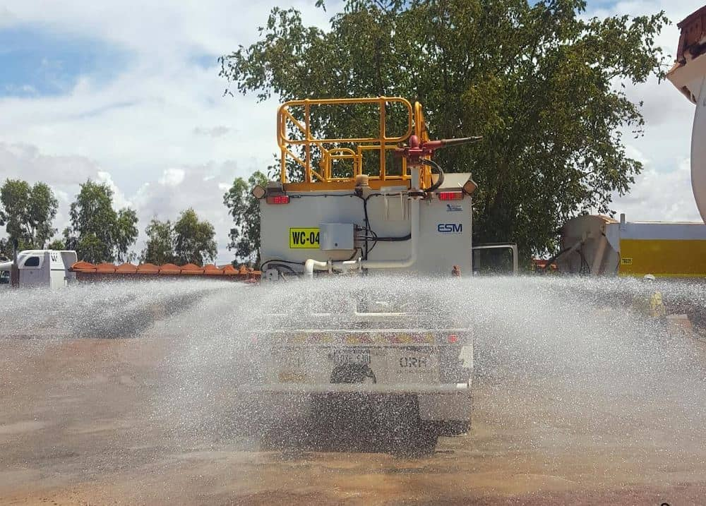 The back of a water cart spraying the ground.